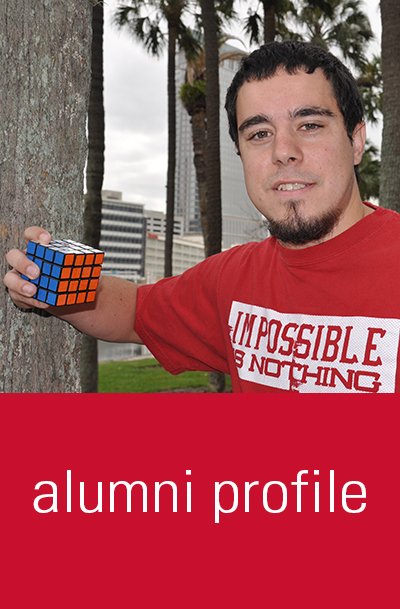 Daniel Ehrmann '14 stands next to a palm tree with a rubix cube in hand.