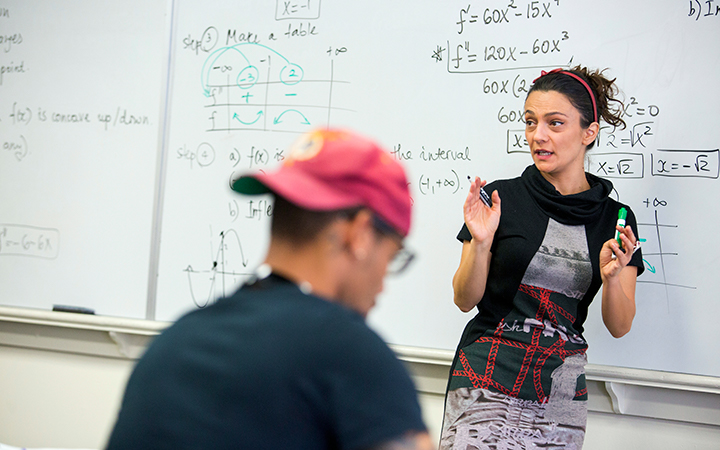 Women professor lectures in front of a male student with a whiteboard full of equations behind her.