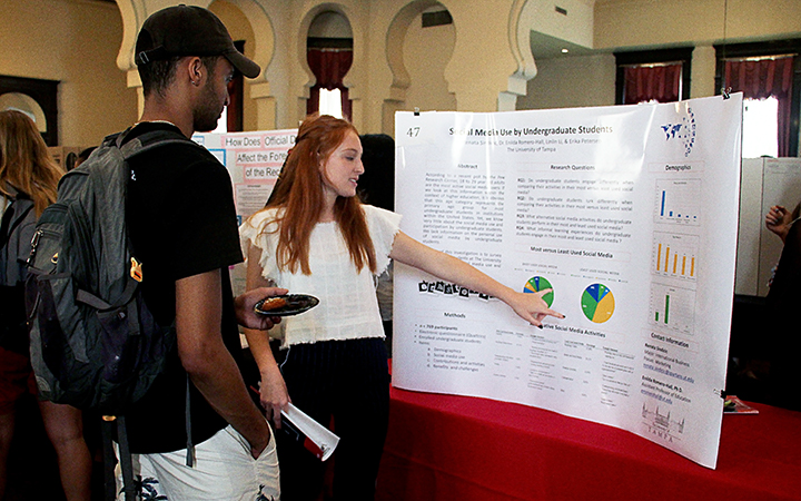 Student points to her poster board to explain her research to another student at the undergraduate research conference.