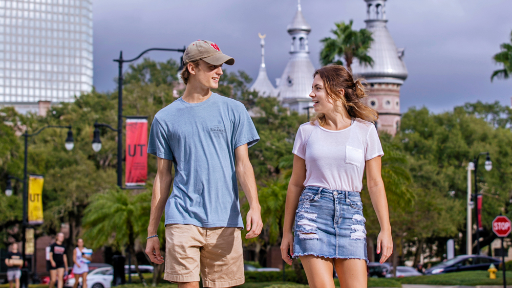 Students walking on campus with minaret and downtown Tampa behind them