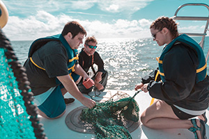 Students examining findings in Tampa Bay on vessel