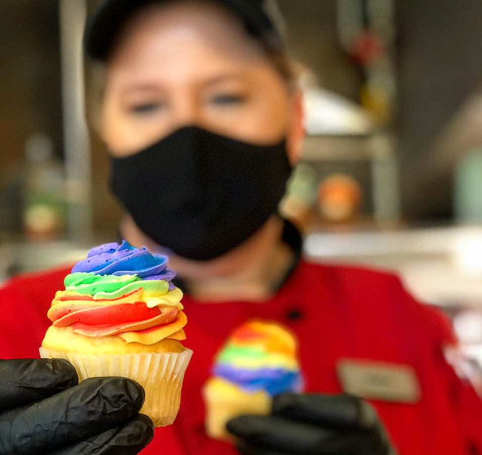 A dining services member offering a cupcake while wearing a mask and gloves.