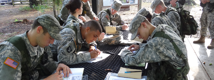 Soldiers sitting at a table doing an assignment