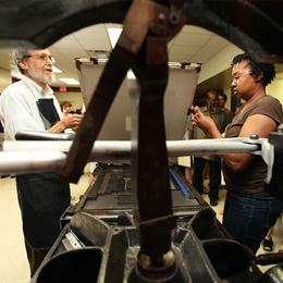 MFA faculty Richard Mathews instructs Kossiwa<br/> Logan in printing a broadside<br/> of Arthur Flowers' work.<br/>