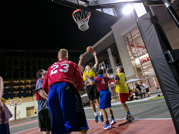 Students playing on the basketball courts at night