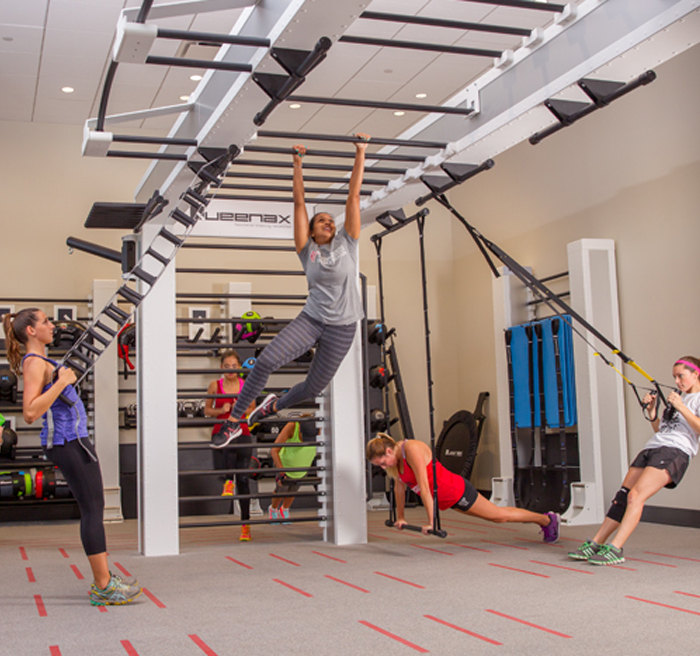 women stretching, lifting weights, and climbing on money bars