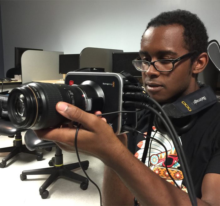 student working with camera in classroom