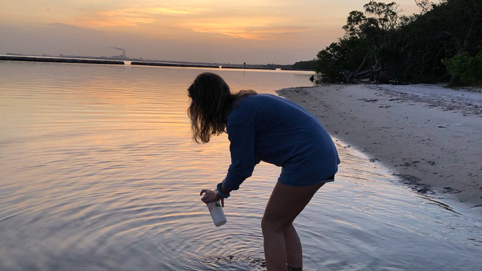 Haley Kudzmas '21 taking a water sample at Gandy Beach